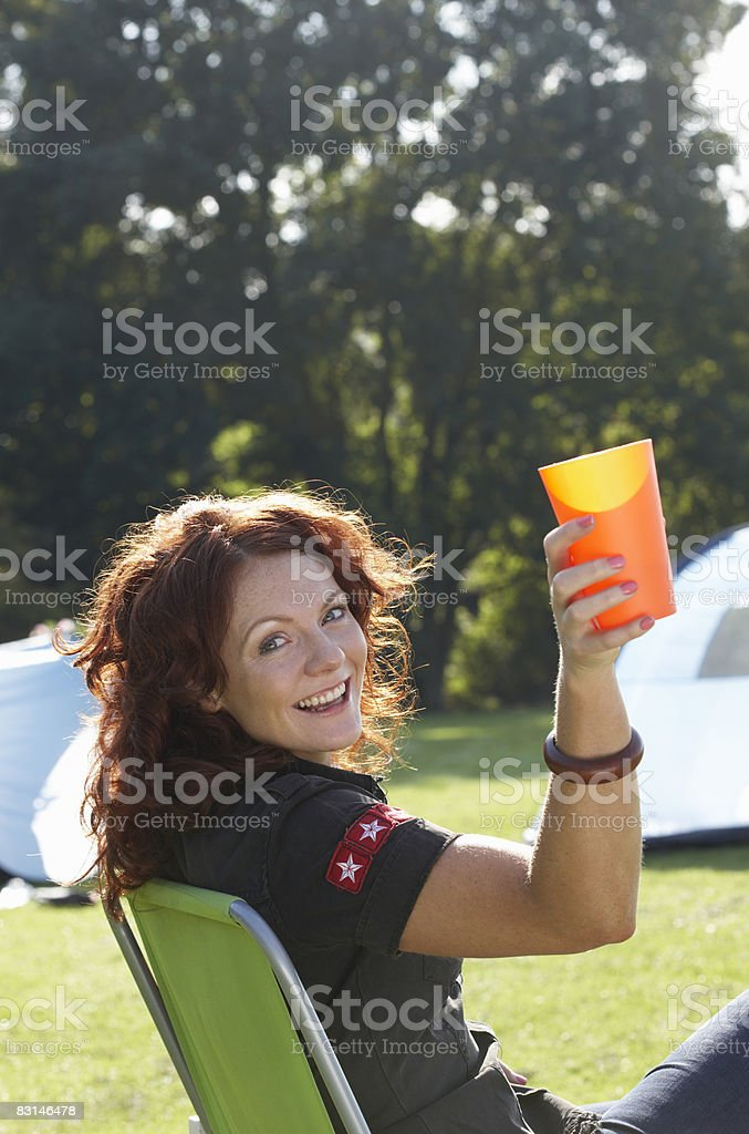 Woman smiling and toasting with a drink royaltyfri bildbanksbilder