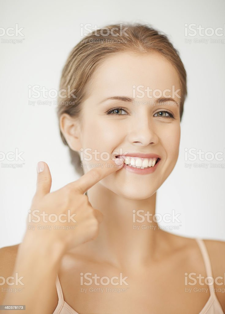 A woman smiling and touching her teeth stock photo