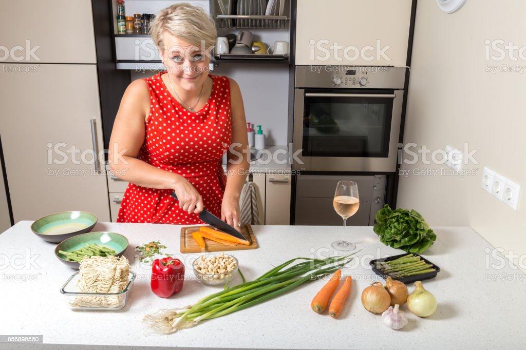 Woman smiling at camera and preparing food stock photo