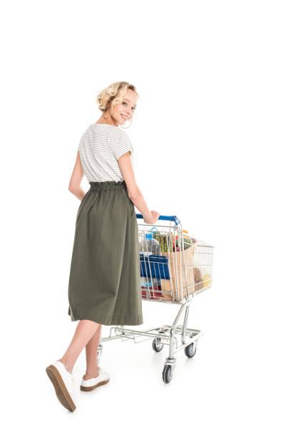 frau lächelt in die kamera und einkaufswagen schieben - trolley kaufen stock-fotos und bilder