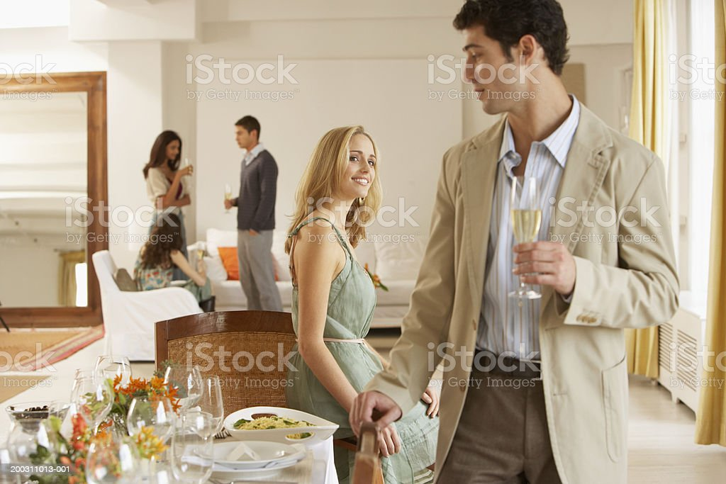 Woman smiling at man standing by dining table, friends in background stock photo