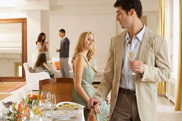 Frau lächelnd im Mann stehend mit Esstisch, Freunden – Foto