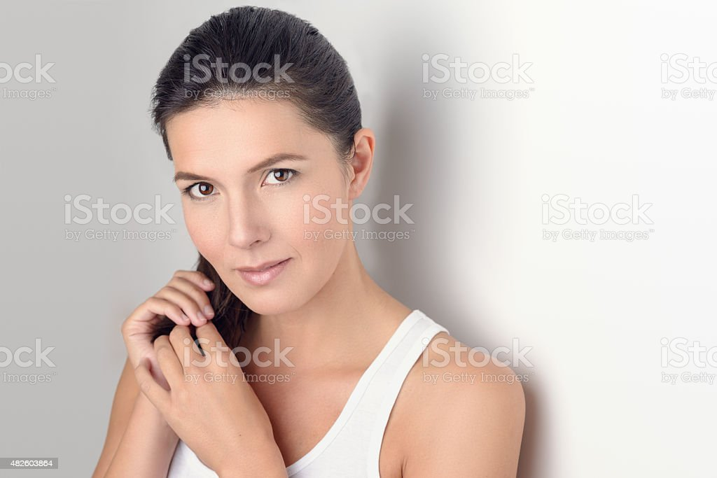 Woman Smiling at the Camera While Holding her Hair stock photo