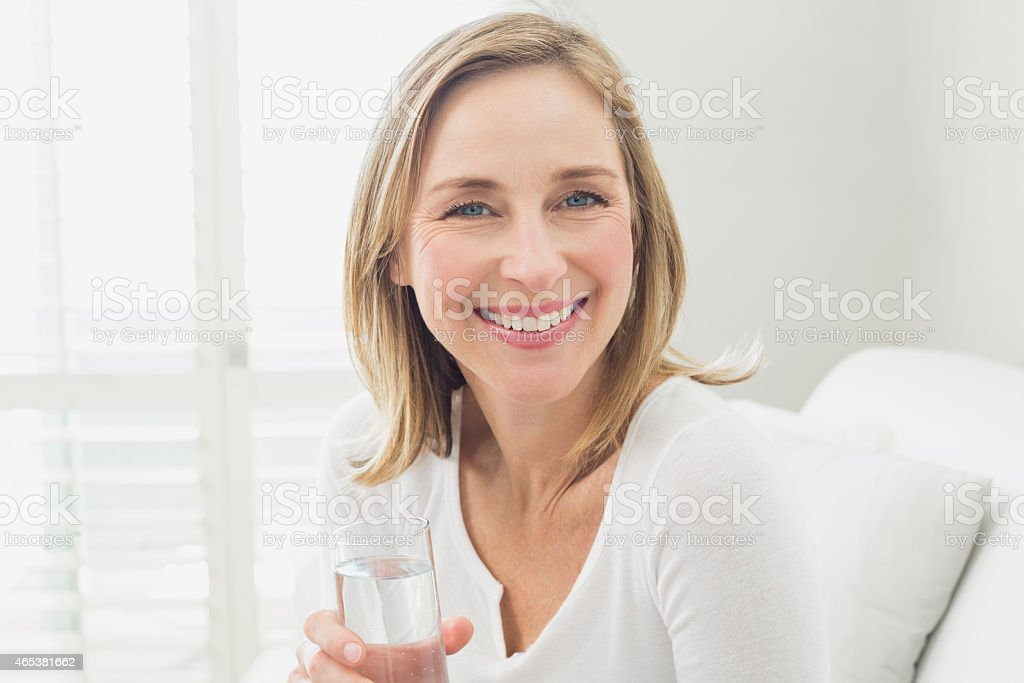 A woman smiling at the camera with glass of water stock photo