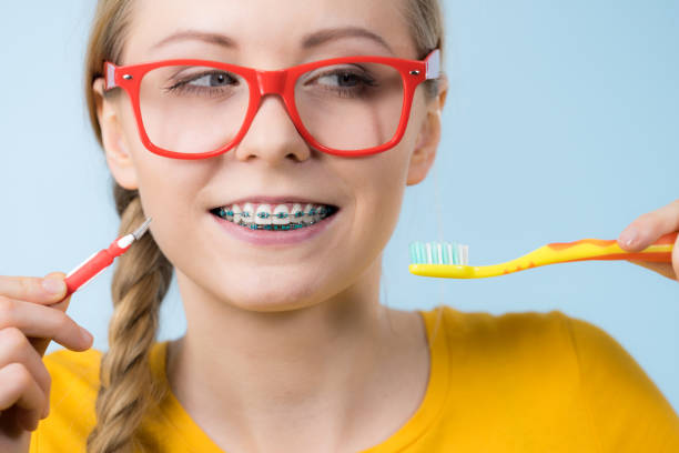 mulher sorrindo limpeza dentes com aparelho - escova interdental - fotografias e filmes do acervo
