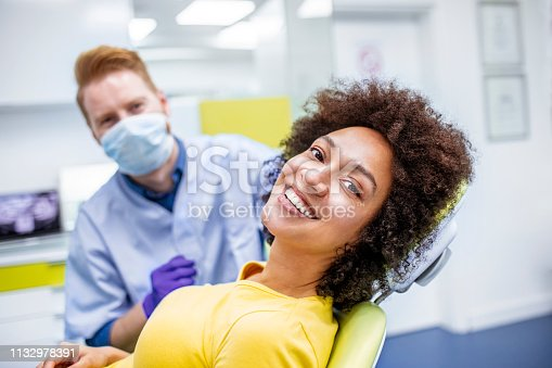 Woman visiting her dentist for a dental checkup. She is smiling.