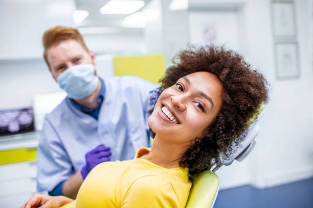 Woman smiling during dental checkup Woman visiting her dentist for a dental checkup. She is smiling. dentist stock pictures, royalty-free photos & images