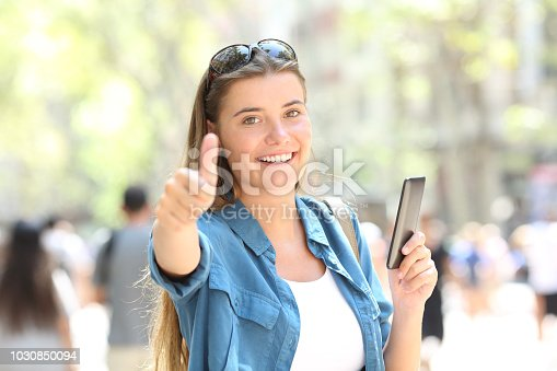 693589426istockphoto Woman smiling holding a smart phone with thumb up 1030850094