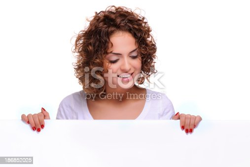 istock Woman smiling holding white blank sign billboard 186852025