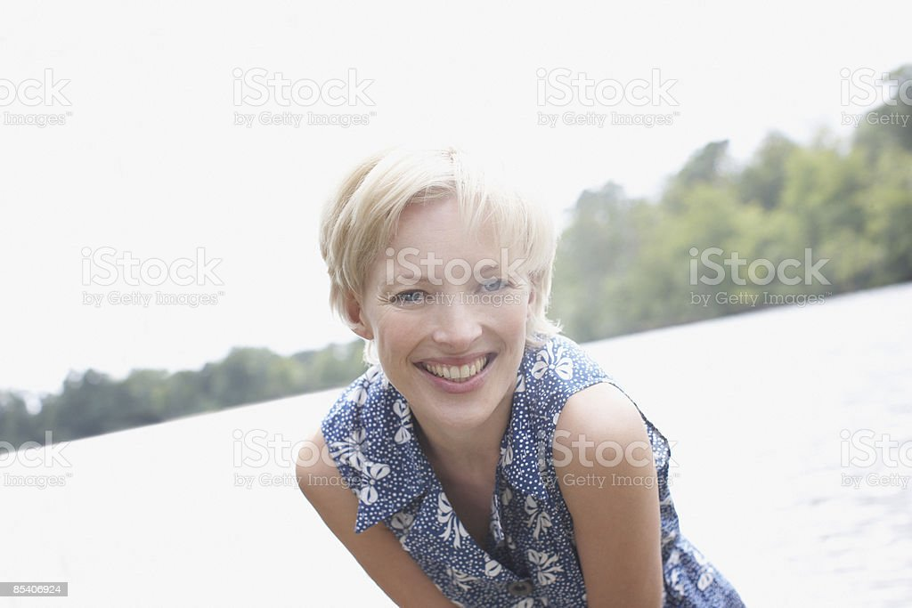 Woman smiling near lake royalty-free stock photo