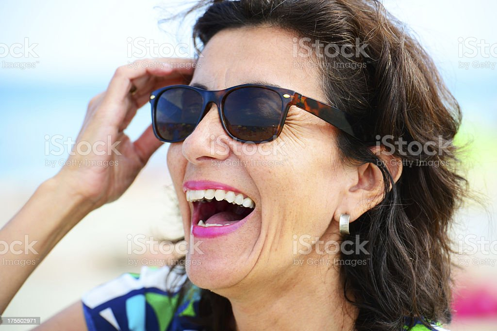 Woman smiling, on beach stock photo
