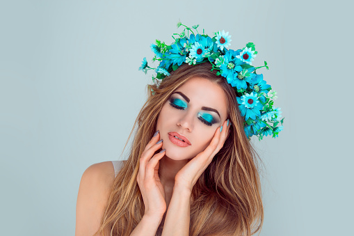istock woman smiling posing with flowers on head blue eyeshadow closed eyes 1128119264