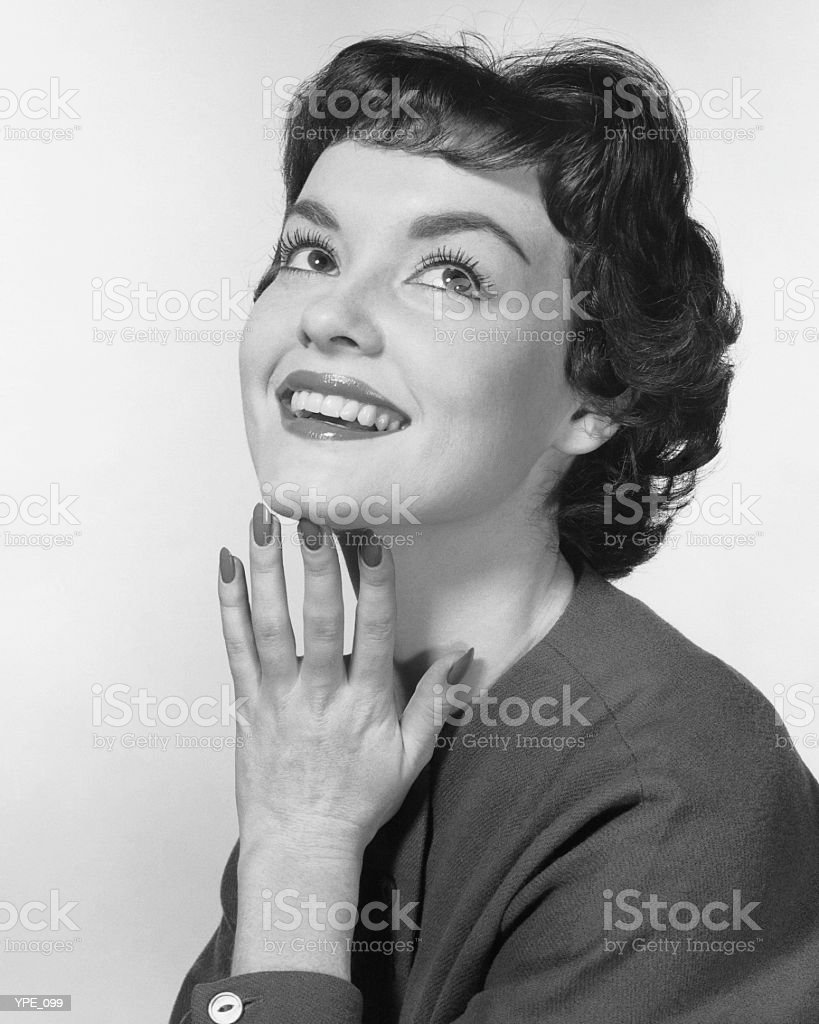 Woman smiling, posing with hand under chin royalty-free stock photo