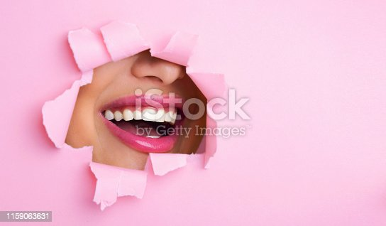 Makeup Concept. Woman Smiling Through Hole In Pink Paper, Free Space