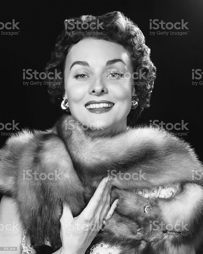 Woman smiling, wearing fur stole royalty free stockfoto