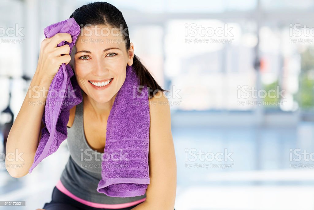Woman Smiling While Cleaning Sweat From Forehead In Gym stock photo