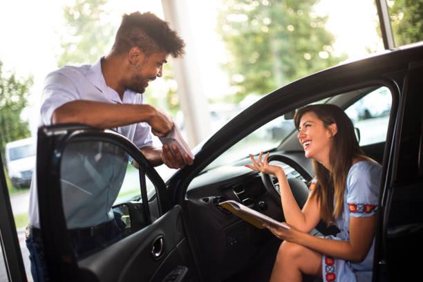 Eine Frau lächelt, während sie mit einem Autoverkäufer in einem Autohaus-Salon über die Bezahlungsraten für ein neues Auto spricht – Foto