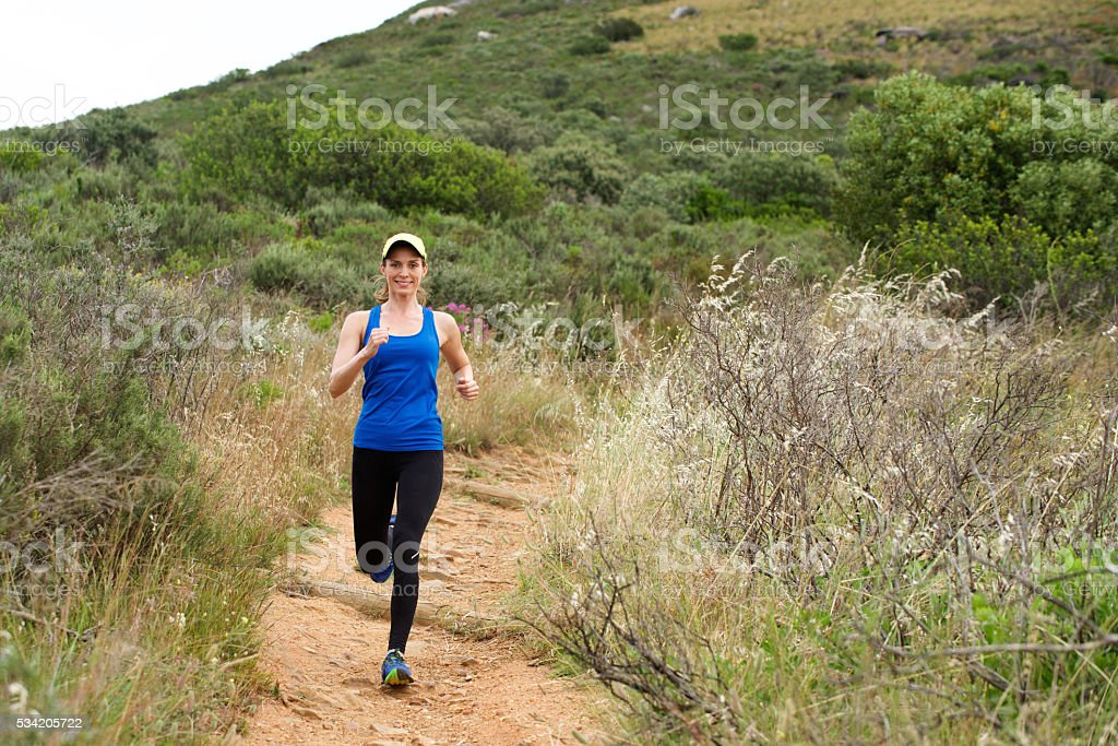 Woman smiling while exercising outside on dirt path stock photo