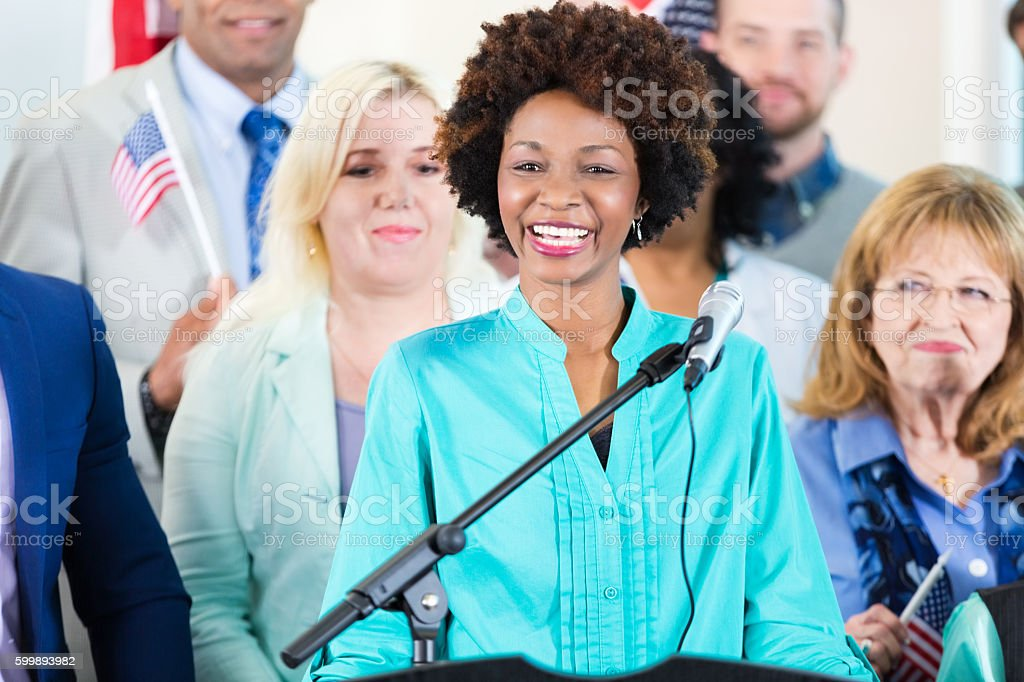 Woman smiling while speaking at local political rally or event - foto de acervo