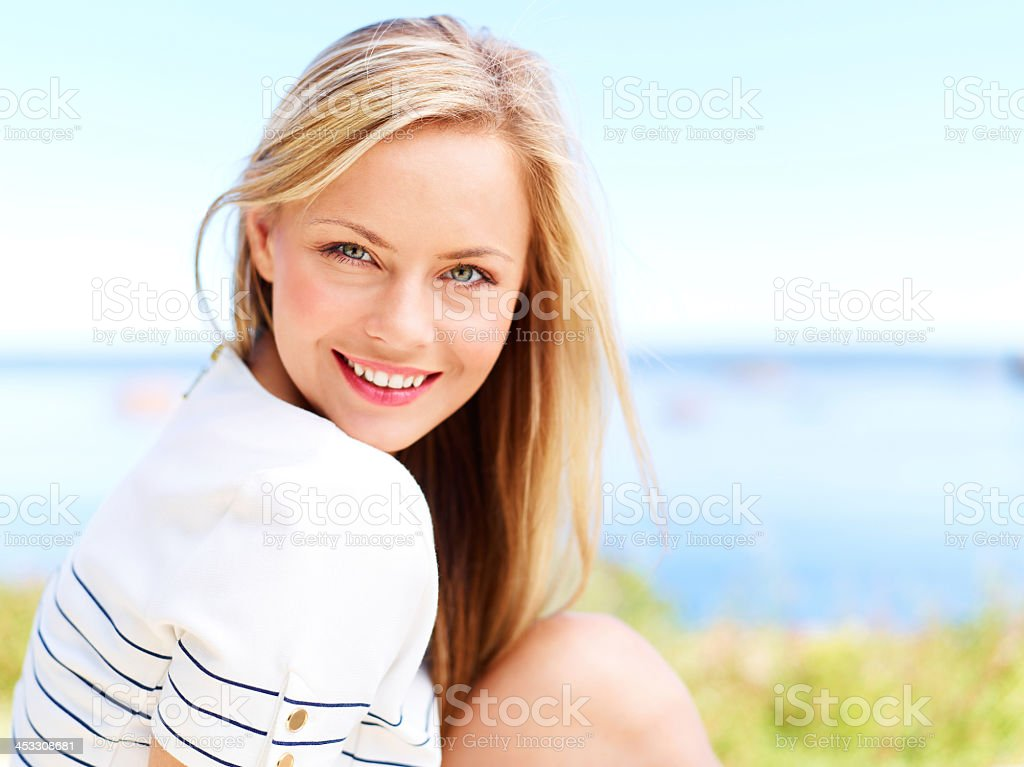 Woman smiling with grass and water blurred background  stock photo