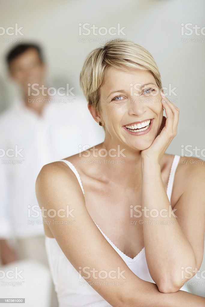 Woman smiling with husband standing in the background royalty-free stock photo