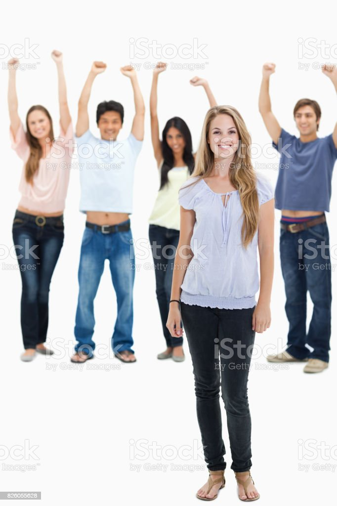 Woman smiling with people with their arms raised behind her stock photo