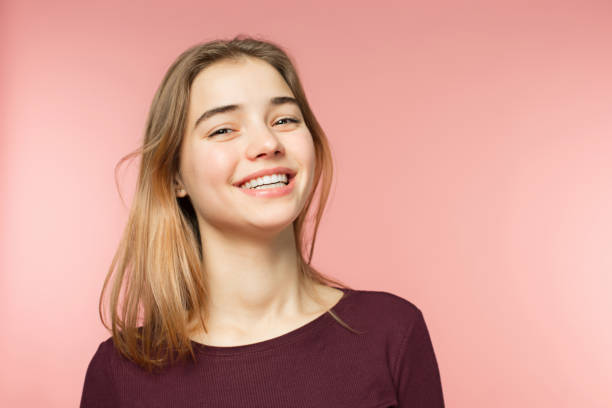 woman smiling with perfect smile and white teeth on the pink studio background and looking at camera - ragazzi adolescenti foto e immagini stock