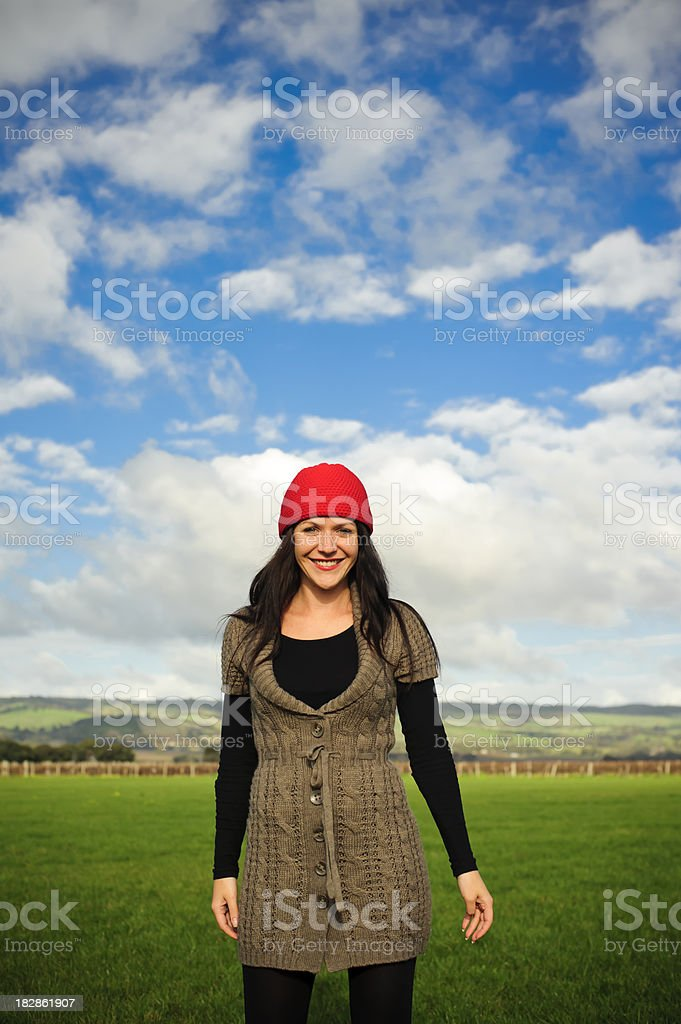 Woman smiling with red wool hat and brown hair stock photo