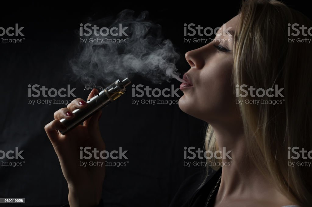 Woman smoke electronic cigarette stock photo