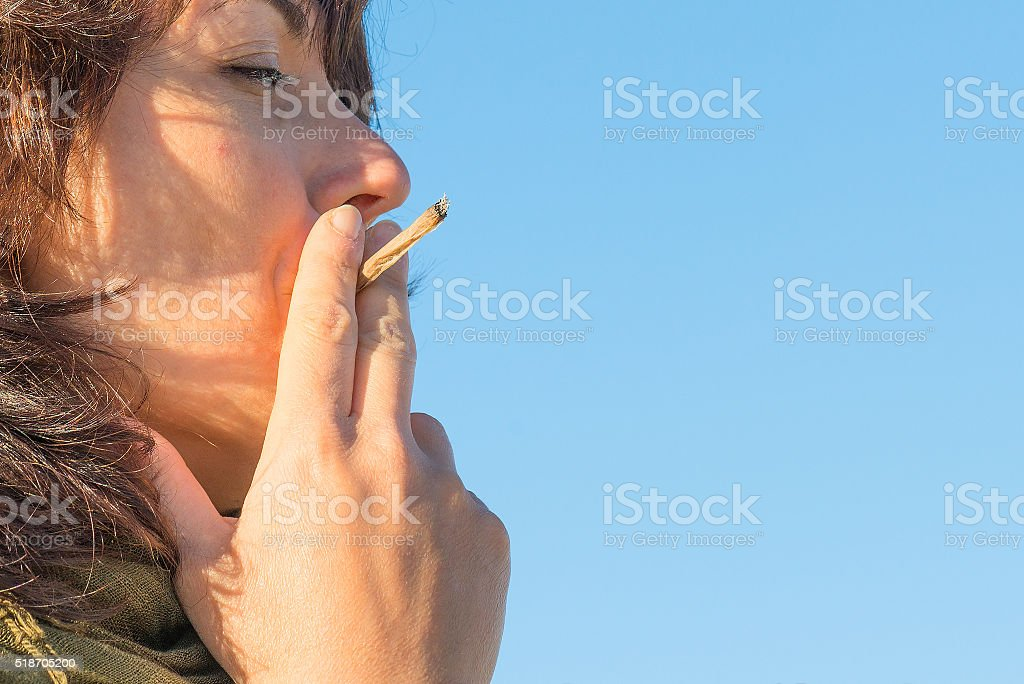 Woman smoking a joint stock photo
