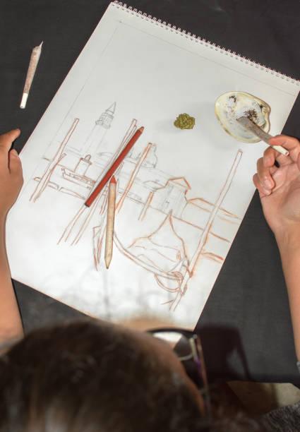 frau raucht einen marihuana joint während einer pause nach dem zeichnen. hintergrund mit cannabisknospe, skizze und muschelaschenbecher. konzept der drogen in der kunst. - bemalte muscheln stock-fotos und bilder