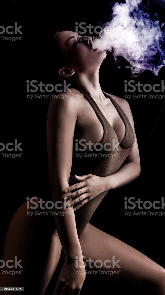 Woman Smoking an E-Cigarette with vapor stock photo