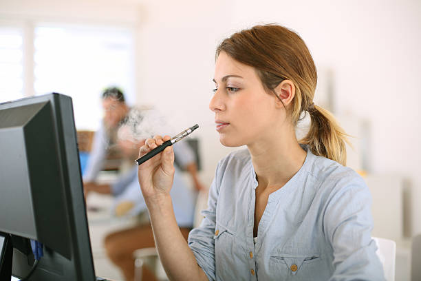 Woman smoking electronic cigarette at work stock photo