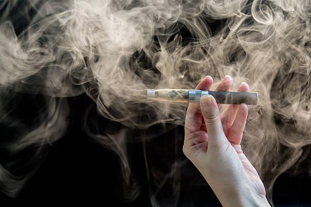 woman smoking electronic cigarette on background - 전자담배 뉴스 사진 이미지