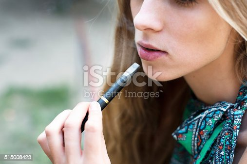 istock Woman smoking electronic cigarette outdoor 515008423