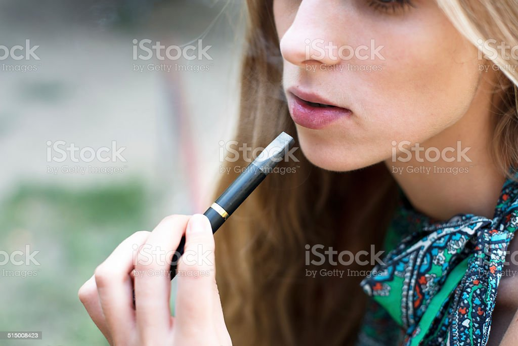 Woman smoking electronic cigarette outdoor stock photo