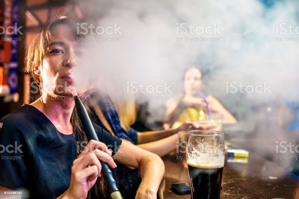 Woman smoking hookah in the bar stock photo