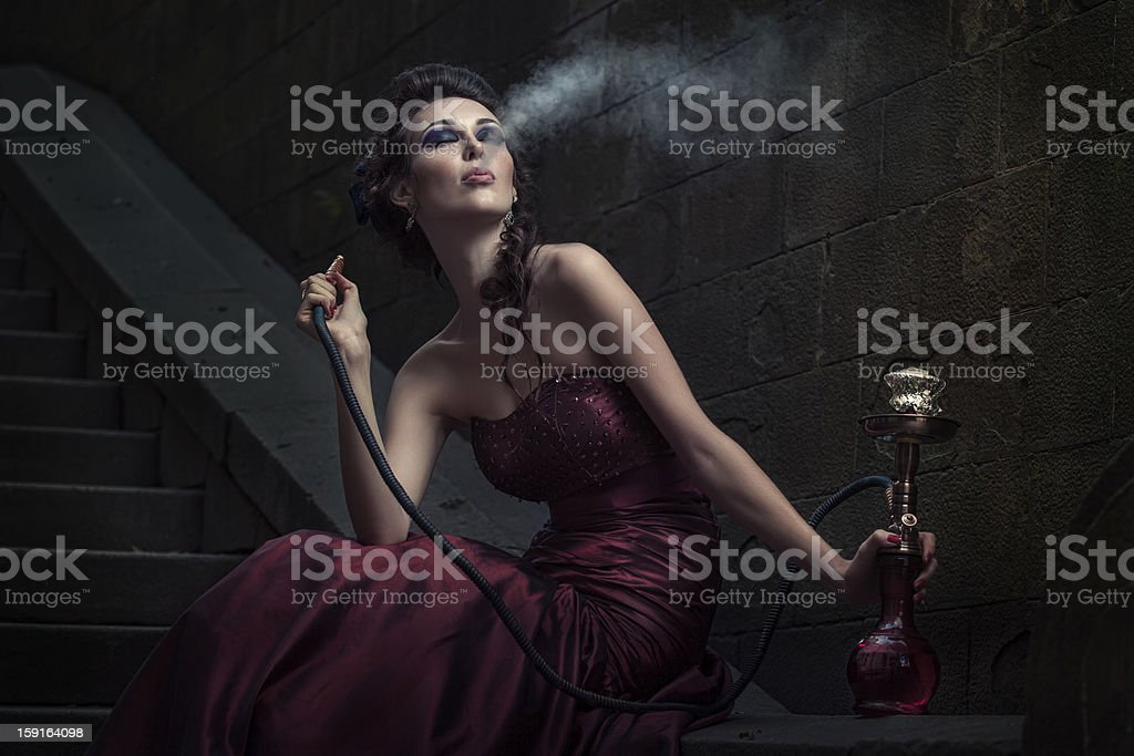 Woman smoking in Victorian purple dress stock photo
