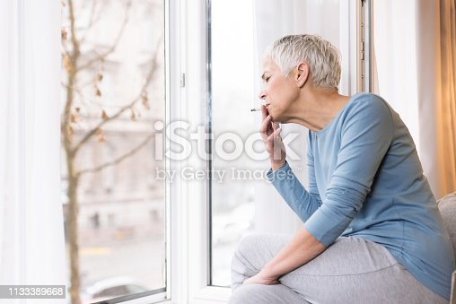 Mindful mature woman sitting by the window in her home and smoking cigarette, Unhealthy habits concept