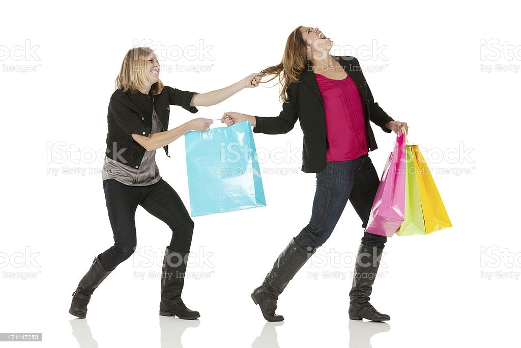 Woman snatching shopping bag from her friend royalty-free stock photo