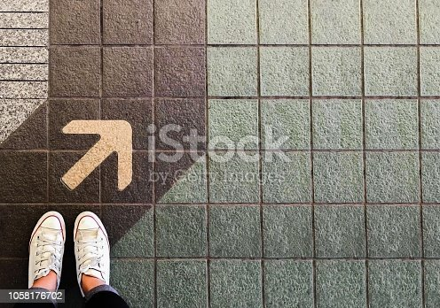 istock Woman sneaker shoe and Arrow on street with copy space background 1058176702