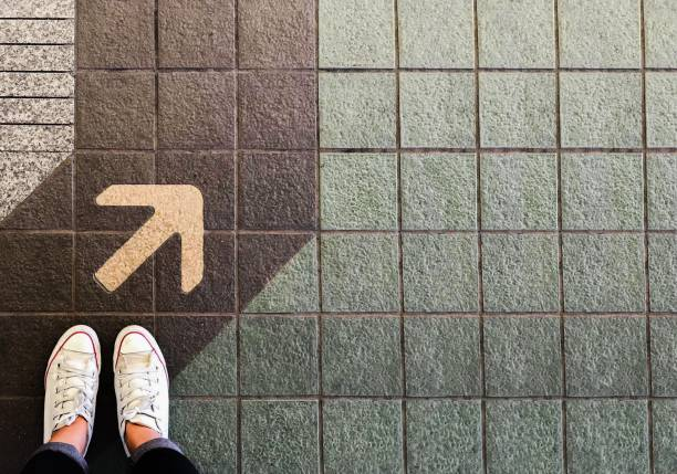 Woman sneaker shoe and Arrow on street with copy space background Woman sneaker shoe and Arrow on street with copy space background the way forward stock pictures, royalty-free photos & images