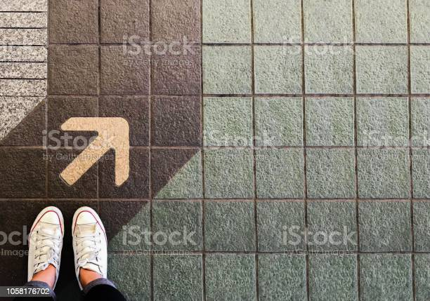 Photo of Woman sneaker shoe and Arrow on street with copy space background