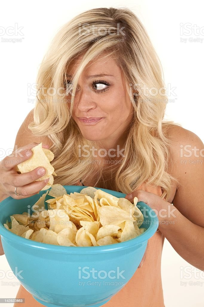 Woman sneaking chips royalty-free stock photo