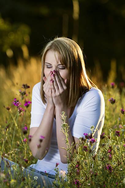 Woman sneezes with allergies stock photo