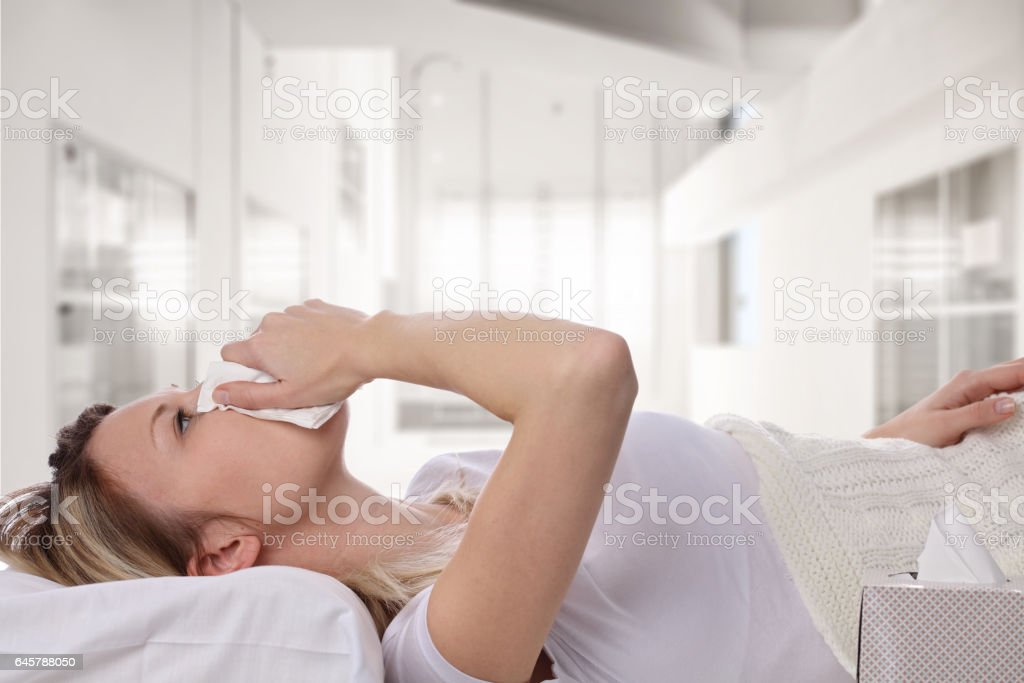 Woman sneezing and holding tissue ,flu symptoms. Healthcare and medical concept stock photo