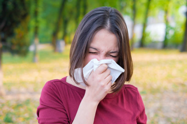 Woman sneezing in a kleenex because of cold and flu Woman sneezing in a kleenex because of seasonal allergy respiratory disease stock pictures, royalty-free photos & images