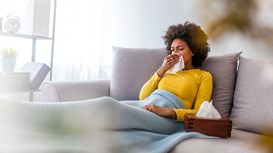Woman Sneezing In A Tissue In The Living Room Stock Photo - Download Image Now