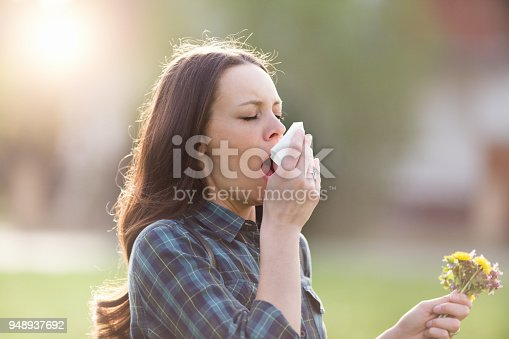 istock Woman sneezing in park with flowers in other hand 948937692