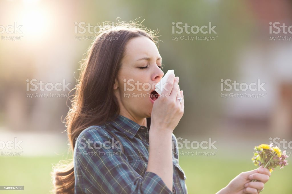 Woman sneezing in park with flowers in other hand stock photo